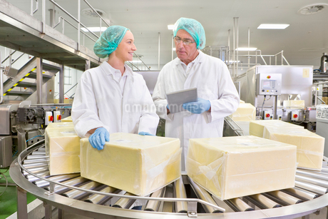 Quality control workers with digital tablet examining blocks of cheese at production line in processの写真素材 [FYI02692479]