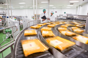 Workers talking behind packages of cheese moving on conveyor belt in processing plantの写真素材 [FYI02692481]