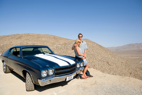 Young couple arm in arm leaning on car in desert looking at view, elevated viewの写真素材 [FYI02692492]