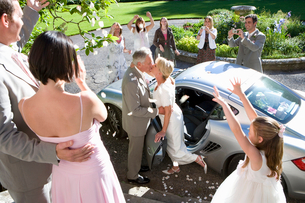 60's couple celebrating marriage next to car surrounded by family throwing petals,の写真素材 [FYI02692509]