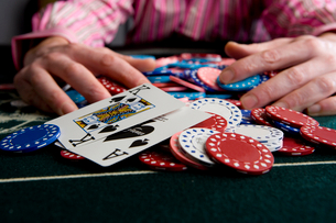 Man collecting pile of gambling chips on table, close-up of winning cardsの写真素材 [FYI02692512]