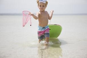 Young boy pulling body board on beachの写真素材 [FYI02692517]