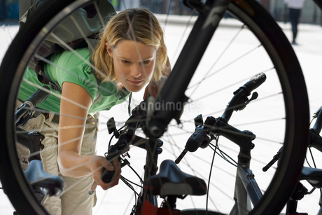 Young woman shopping for new bike in bicycle shopの写真素材 [FYI02692531]