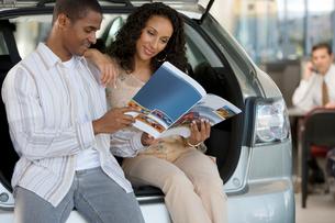 Salesman in car showroom, focus on couple looking at brochure beside new hatchback in foregroundの写真素材 [FYI02692536]