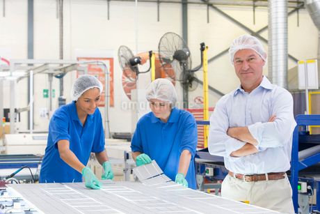 Businessman smiling at camera and technician workers arranging solar cells to form solar panel on prの写真素材 [FYI02692546]