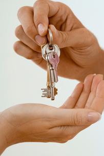 Man handing woman set of keys, close-up of hands, side viewの写真素材 [FYI02692564]