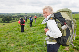 Portrait of smiling girl with backpack in fieldの写真素材 [FYI02692599]