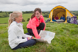Smiling girls using compass and map next to tent in rural fieldの写真素材 [FYI02692601]