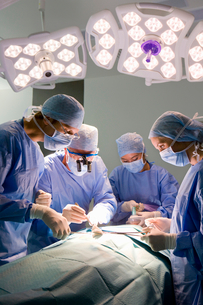 Concentrating surgeons performing operation in operating roomの写真素材 [FYI02692602]