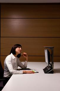 Pensive businesswoman sitting at deskの写真素材 [FYI02692604]