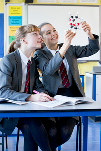 Smiling high school students examining molecule model in science classの写真素材 [FYI02692613]