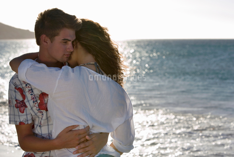 Affectionate teenage couple (17-19) embracing on beach near water's edgeの写真素材 [FYI02692619]