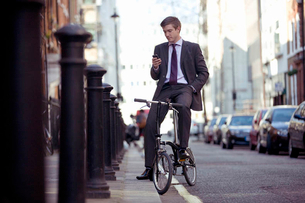 A businessman on his bicycle, looking at his mobile phoneの写真素材 [FYI02692627]