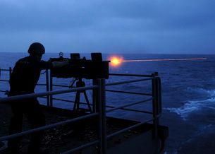 A sailor fires a .50-caliber machine gun on the fantail of Uの写真素材 [FYI02692632]