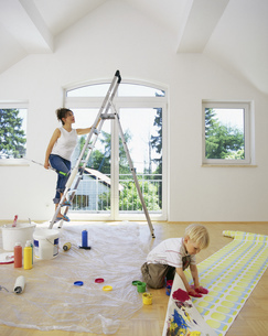 Portrait of a young woman on a ladder as her son fingerpaints on a roll of wallpaperの写真素材 [FYI02692636]