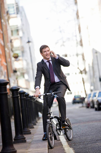 A businessman on his bicycle, talking on a mobile phoneの写真素材 [FYI02692667]