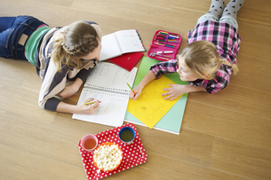 High angle view of two young girls coloring and doing homework togetherの写真素材 [FYI02692672]
