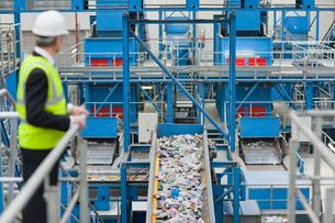 Businessman watching plastic on conveyor belt in recycling plantの写真素材 [FYI02692674]