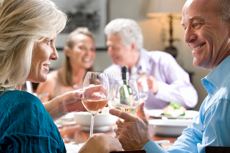 Mature couple toasting wine glasses at dinner table, mature couple smiling in backgroundの写真素材 [FYI02692679]