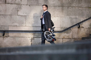 A businessman carrying his folded bicycle to workの写真素材 [FYI02692683]