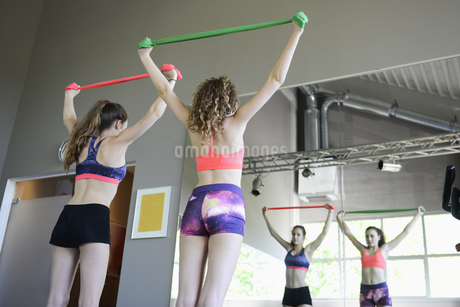Teenage girls stretching with resistance band in gymの写真素材 [FYI02692695]
