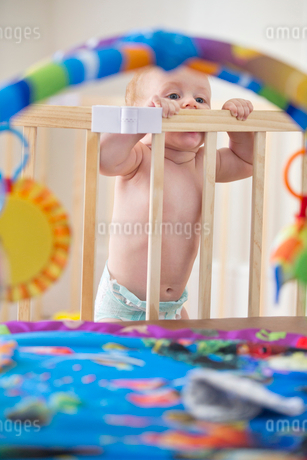 Baby Boy Wearing Disposable Diaper In Wooden Playpen At Homeの写真素材 [FYI02692698]