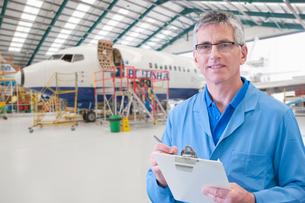 Portrait Of Aero Engineer Working On Aircraft In Hangarの写真素材 [FYI02692699]