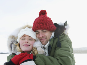 A young couple embracing to keep warm in the snowの写真素材 [FYI02692701]