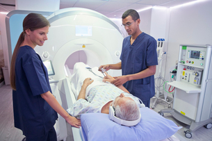 Hospital Radiographers With Male Patient Operating MRI Scannerの写真素材 [FYI02692705]