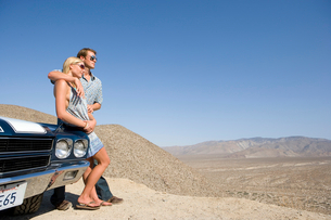 Young couple arm in arm leaning on car in desert looking at view, low angle viewの写真素材 [FYI02692726]