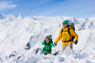 Couple holding hands and backpacking on snowy mountainの写真素材 [FYI02692737]