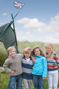 Group Of Children Standing In Dunes Next To Home Made Campの写真素材 [FYI02692755]