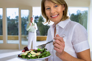 Mature woman eating salad on plate at home, senior man in background, focus on woman, smiling, sideの写真素材 [FYI02692787]