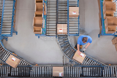 Worker with bar code reader scanning box on conveyor belt in distribution warehouseの写真素材 [FYI02692789]