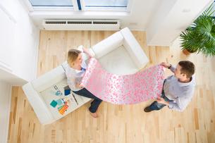 Couple looking at wallpaper sample in living roomの写真素材 [FYI02692792]