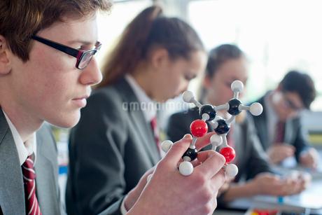 High school student examining molecule model in science classの写真素材 [FYI02692796]