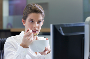 Businesswoman eating cereal and working at computer in officeの写真素材 [FYI02692797]