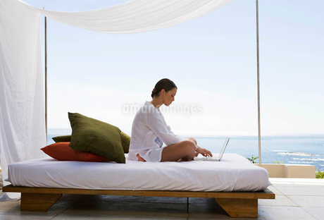 A young woman sitting on a bed with a laptopの写真素材 [FYI02692806]