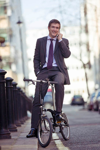 A businessman on his bicycle, talking on a mobile phoneの写真素材 [FYI02692815]