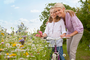 Mother and daughter with bicycle in wildflower fieldの写真素材 [FYI02692822]