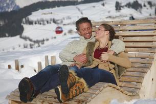 Couple relaxing on wooden chair in ski resortの写真素材 [FYI02692824]