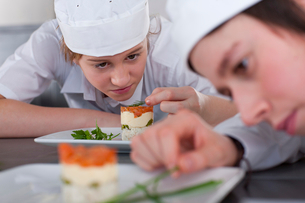 Trainee chef's working together in commercial kitchenの写真素材 [FYI02692833]