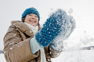 A senior woman playing with snowの写真素材 [FYI02692839]