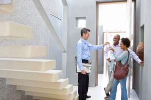 Male real estate agent handing keys to couple, standing by stairs, smiling, side viewの写真素材 [FYI02692844]