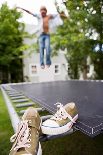 Boy (4-6) jumping on trampoline in garden, arms out, focus on plimsolls in foregroundの写真素材 [FYI02692857]