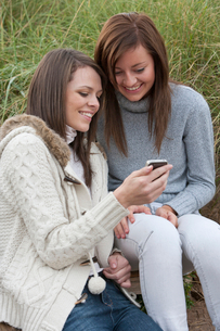 Smiling young women looking at text message on cell phone in grassの写真素材 [FYI02692868]