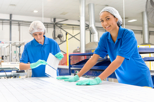 Technician worker smiling at camera arranging solar cells to form solar panel on factory productionの写真素材 [FYI02692873]