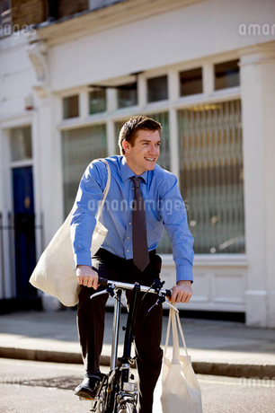 A businessman riding his bicycle, carrying shopping bagsの写真素材 [FYI02692876]