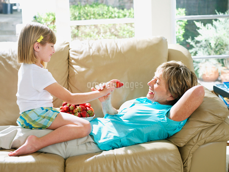 Senior woman lying on sofa at home, granddaughter (6-8) sitting in grandmother窶冱 lap, feeding herの写真素材 [FYI02692898]