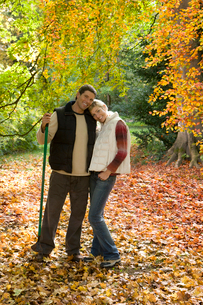 Portrait of couple with rake standing in autumn leavesの写真素材 [FYI02692905]